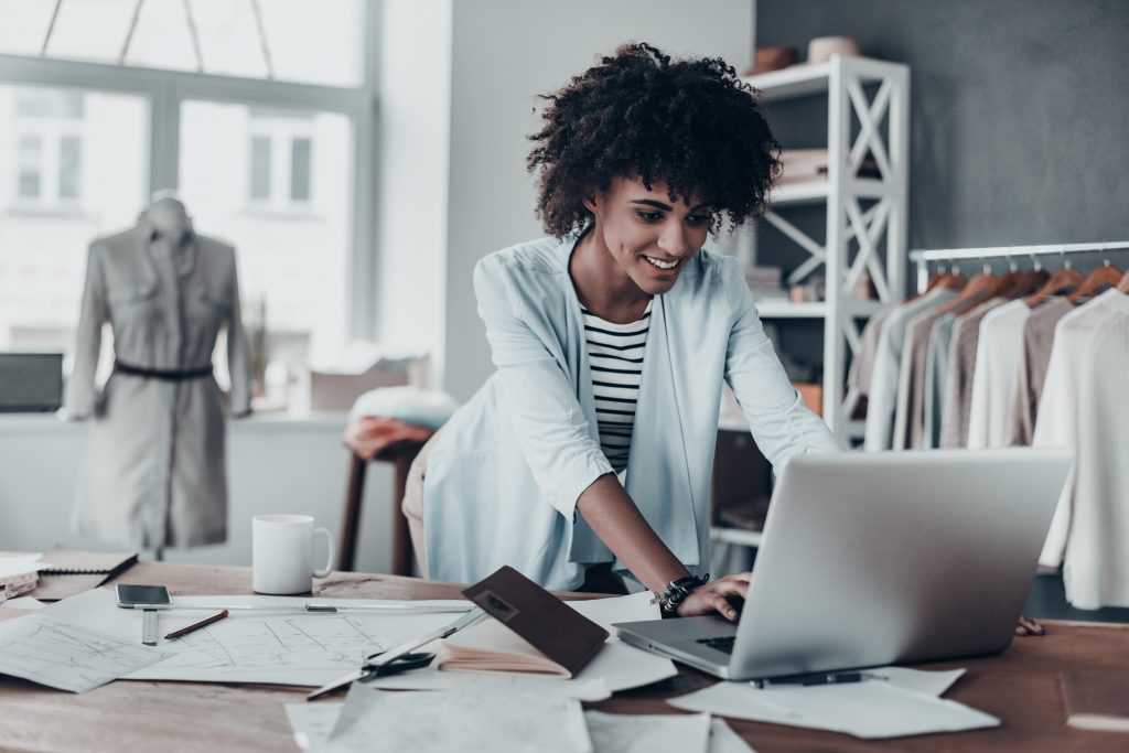 Woman standing at computer desk working on laptop.