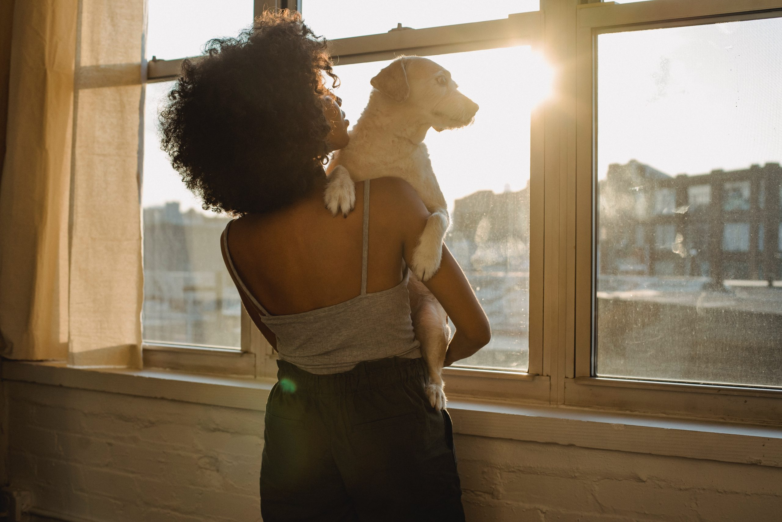 Woman holding dog in front of window