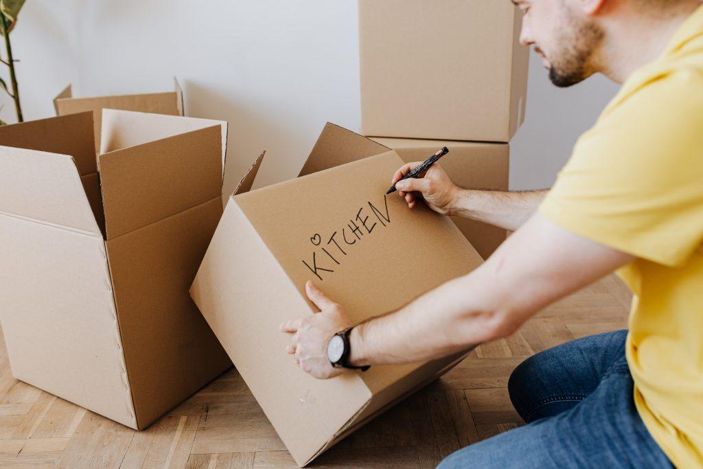 Man writing Kitchen on box