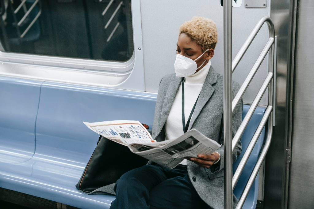 Woman in subway wearing a mask.